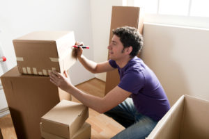 man labeling his moving boxes